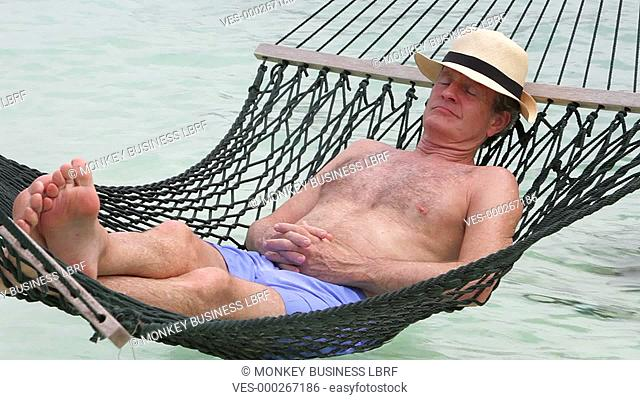 Senior man lying in hammock with eyes closed.Shot on Canon 5d Mk2 with a frame rate of 30fps