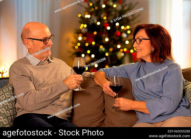 happy senior couple with red wine on christmas