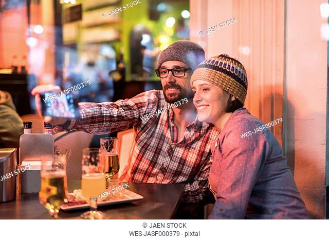 Couple in a winter terrace bar behind a glass taking a selfie