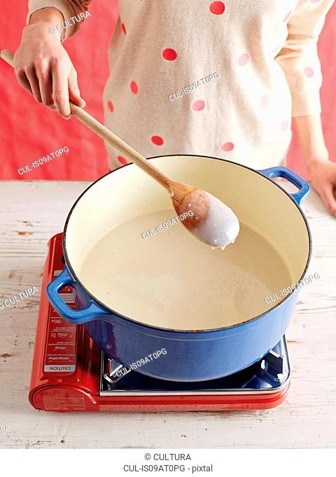 High angle view of mid adult womans mid section making gochuchang in a saucepan