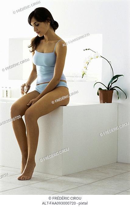Young woman sitting on edge of bathtub, putting moisturizer on leg
