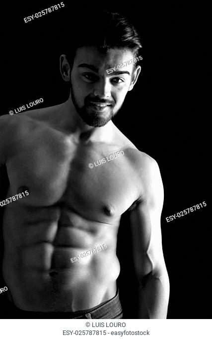 Handsome young man, shirtless, with great body posing over a black background
