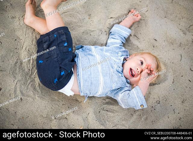 Little boy playing with sand on a California beach