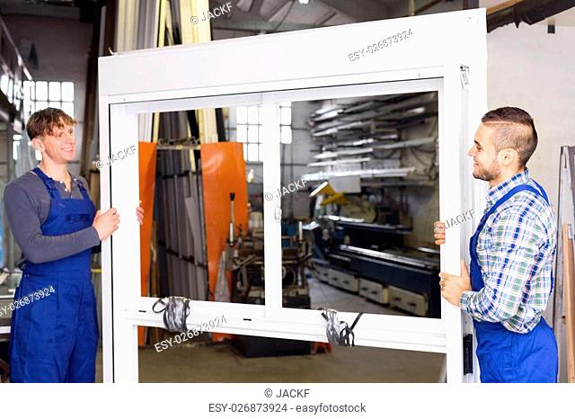 Two adult workers inspect the windows in the workshop