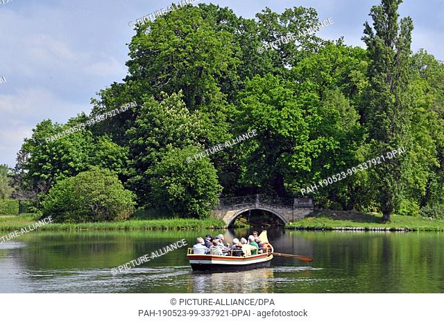 21 May 2019, Saxony-Anhalt, Oranienbaum-Wörlitz: A gondola with tourists travels across the lake in the world-famous Wörlitzer Park