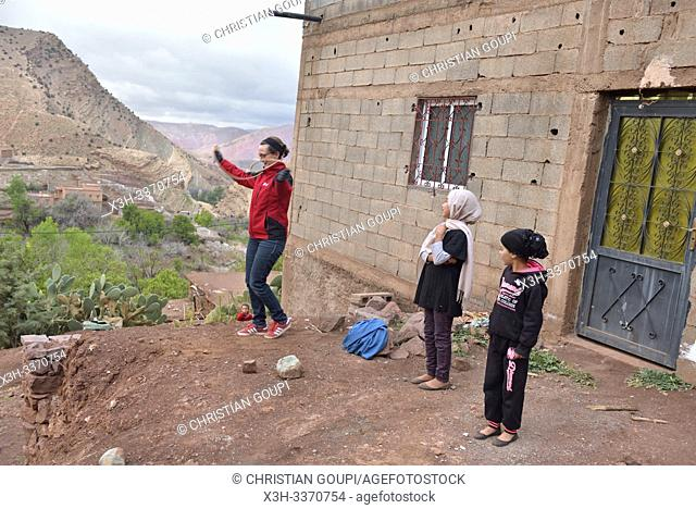 children playing in the compagny of a tourist in the village of Tighza, Ounila River valley, Ouarzazate Province, region of Draa-Tafilalet, Morocco