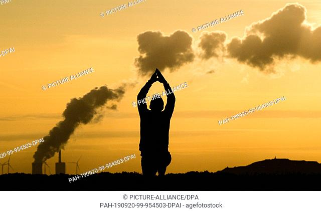 20 September 2019, Lower Saxony, Hanover: A jogger stretches out at Kronsberg shortly after sunrise, while steam rises on the horizon from the Mehrum coal-fired...