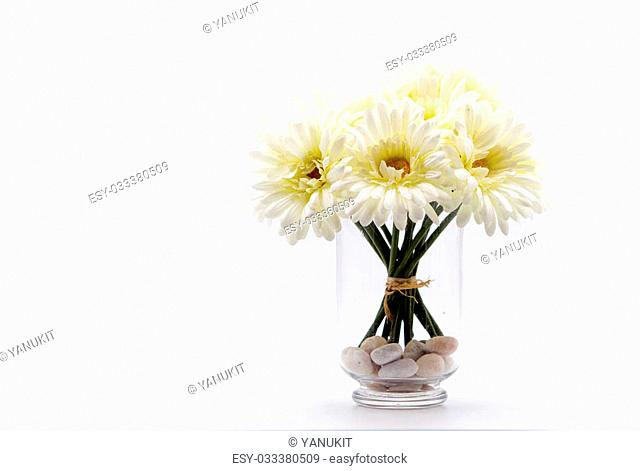 close up artificial white daisy bouquet in glass vase on isolate copyspace