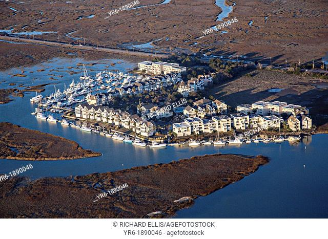 Aerial showing a housing development surrounded by marsh and water in Charleston, SC