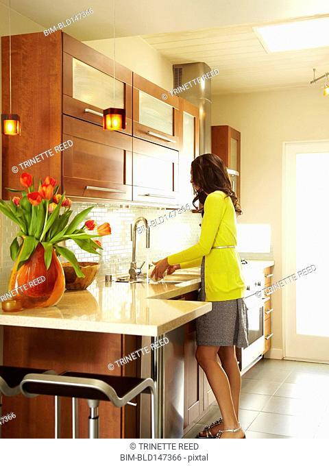 Hispanic woman washing dishes in kitchen