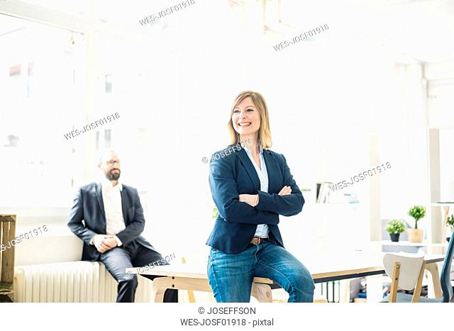 Smiling businesswoman and man in office