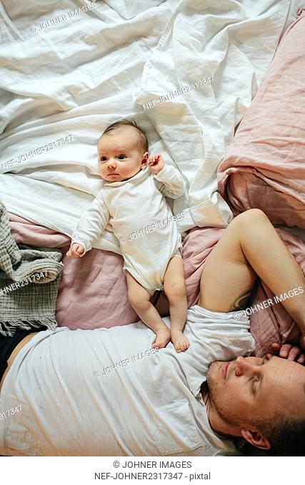 Father with baby in bed