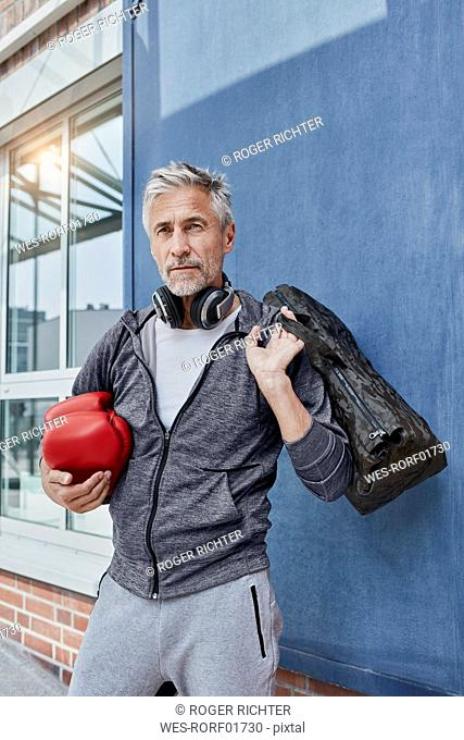 Portrait of mature man with headphones, sports bag and red boxing gloves standing in front of gym