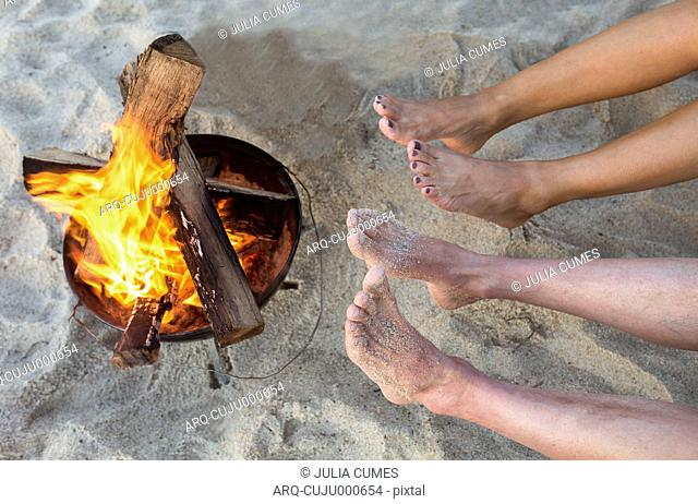 People Warming Their Feet At A Campfire At The Beach
