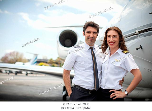 Portrait of male and female private jet pilots at airport