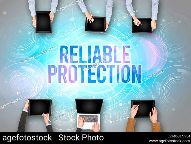 Group of people in front of a laptop with RELIABLE PROTECTION insciption, web security concept