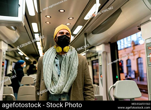 Man wearing protective face mask looking away while standing in train