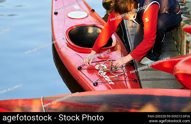 28 March 2020, Brandenburg, Lübben: One of the managers of the boat and second bike rental Gebauer puts her canoe on. It was the only one far and wide on the...