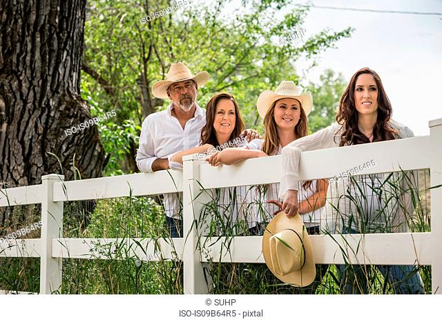 Portrait of mature couple and two daughters in cowboy hats leaning against ranch fence, Bridger, Montana, USA