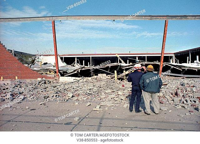 Two firefighters examine a collapsed wall of a warehouse in Landover, Maryland, USA
