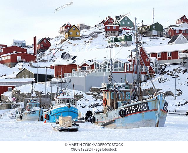 Town Uummannaq during winter in northern Greenland. Ships in the frozen harbour. America, North America, Denmark, Greenland