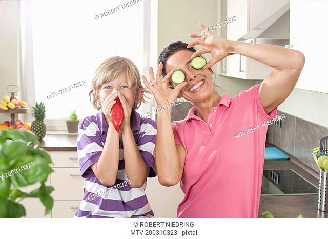 Woman with her son playing with vegetables in kitchen, Bavaria, Germany