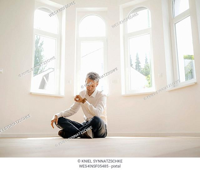 Businessman sitting on ground of his newly refurbished home, checking time