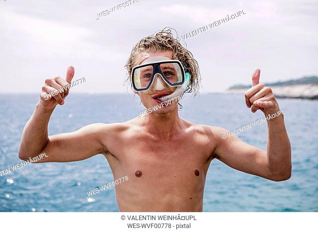 Portrait of smiling young man with diving goggles and snorkel showing Rock And Roll Sign