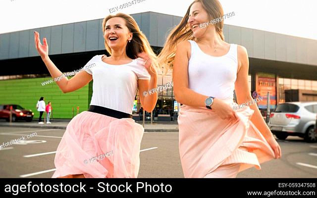 Portrait of two laughing cheerful girls in same outfit playing and having fun on car parking at shopping mall