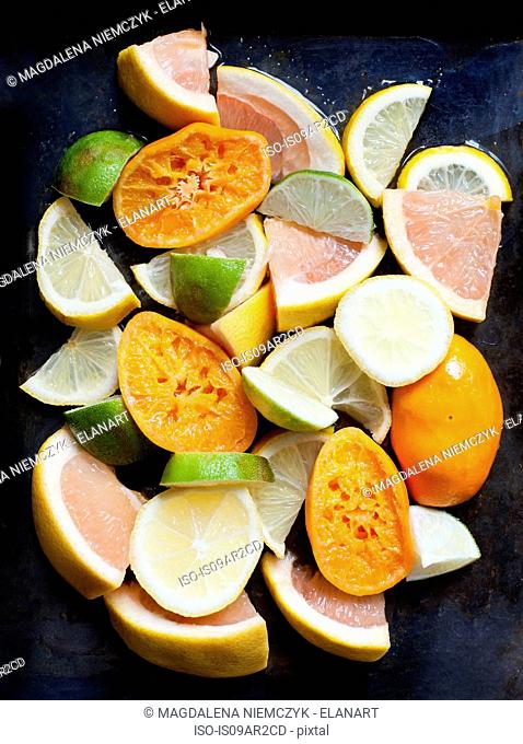 Stack of squeezed oranges, with sliced grapefruit lime and lemons