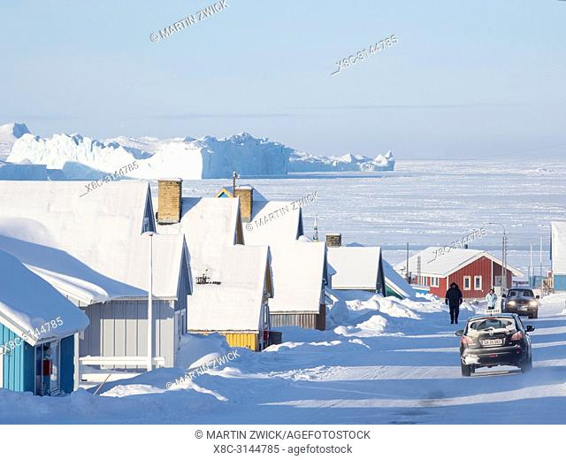 Streets in town, frozen Disko Bay with icebergs in the background. Town Ilulissat at the shore of Disko Bay in West Greenland, center for tourism