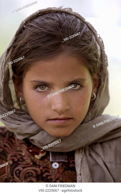 A young nomadic Bakharwalli shepherd girl with an intense stare passes through the small Kashmiri village of prang. - PRANG, KASHMIR, INDIA, 23/06/2010