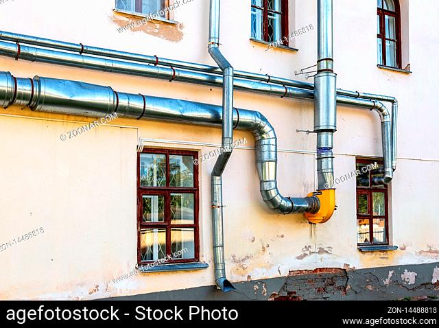 Metal pipes for ventilation and water mounted on the wall of building