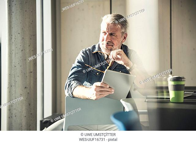 Casual mature businessman sitting at desk with tablet