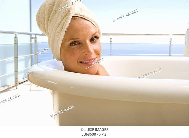 Young woman lying in bath outdoors, towel on head, smiling, portrait, close-up