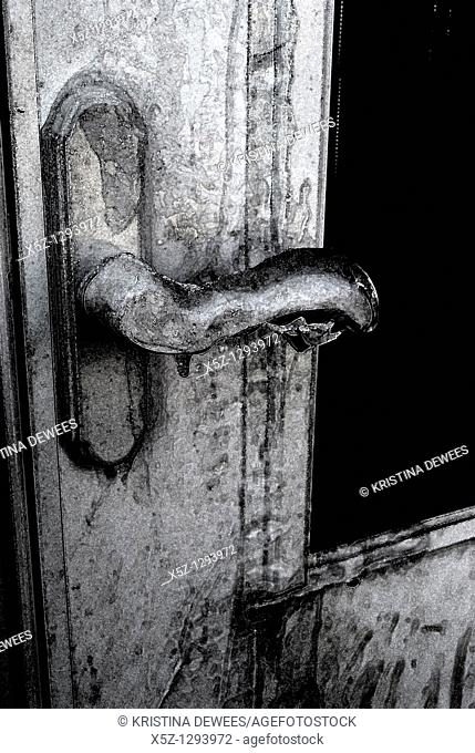An ice covered door handle in the Winter with effects