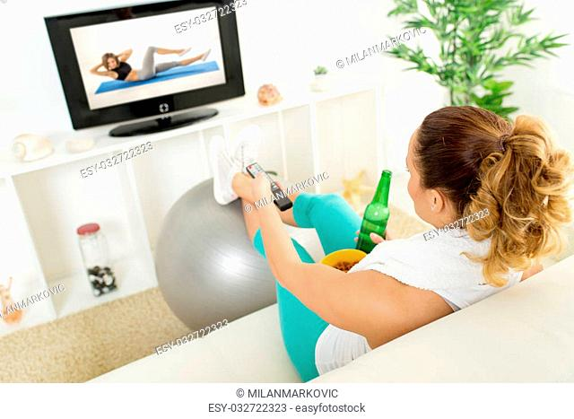Lazy woman in sport clothing sitting front of the TV and doesn't wont to exercise