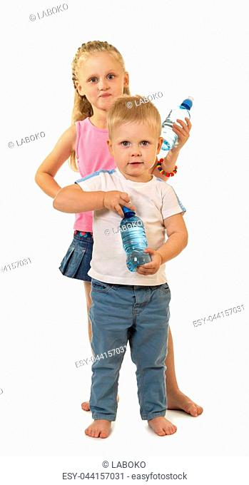 Barefoot boy and girl are standing side by side, holding water bottle isolated on white background