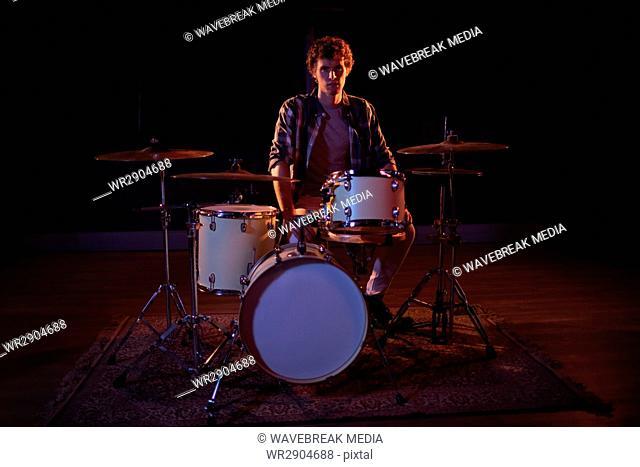 Portrait of drummer sitting with drum set