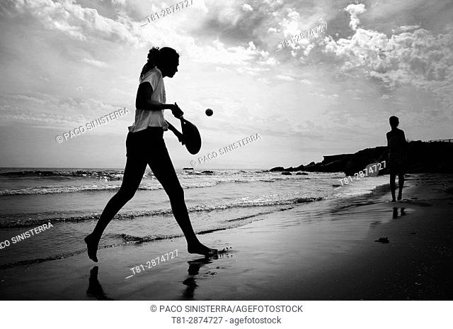 Girl, Young man playing the shovels on the beach of Alcocebre, Castellon