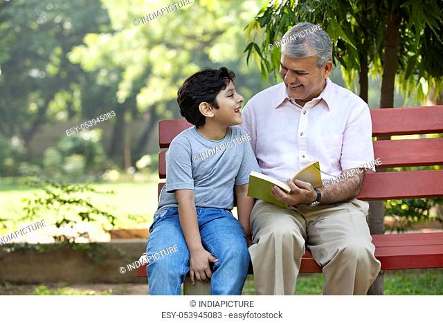 Grandfather and grandson sitting in a park