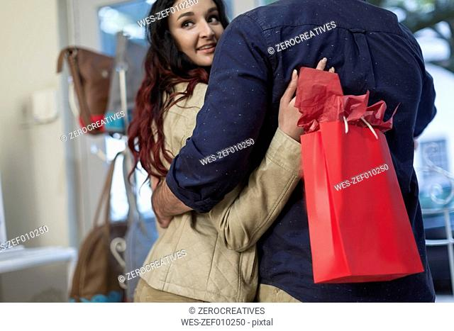 Couple leaving store with shopping bag