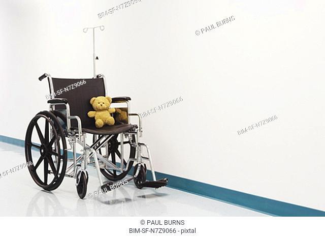 Wheelchair with teddy bear in hospital corridor