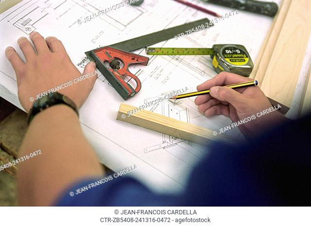 Woodworker making notes on plans