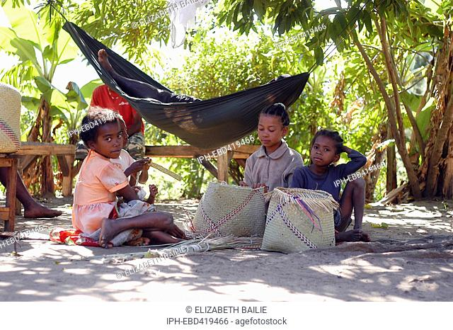 Madagascar Anosy Region Young girls weave baskets in the shadows of the palm trees in Mahialambo