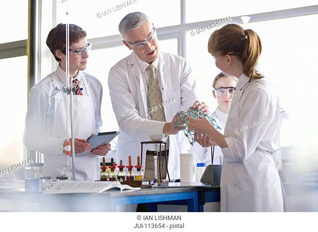 Chemistry teacher helping high school students conducting scientific experiment