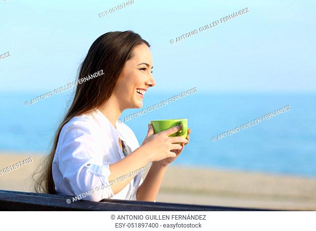 Side view portrait of a single happy woman holding coffee and looking away on the beach