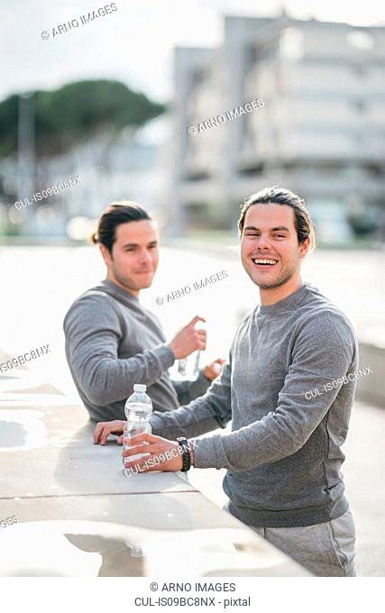 Young adult male twins taking a training break, portrait