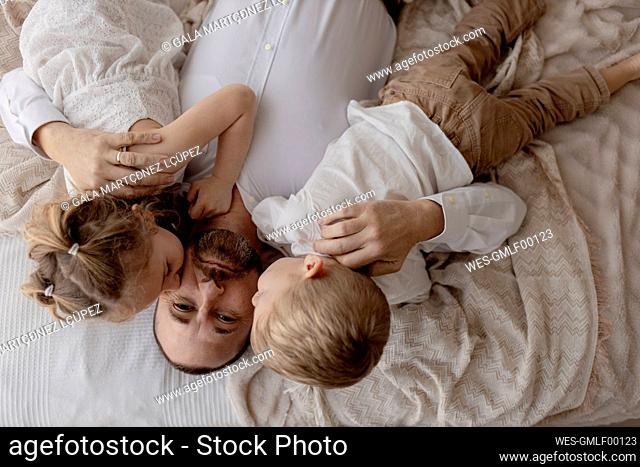 Portrait of father lying on bed kissed by his two children