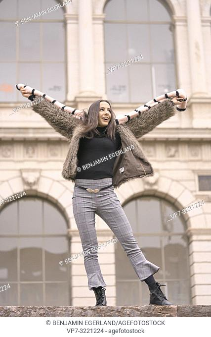 playful woman in fashionable winter clothes, playing with scarf, happy, in front of wealthy historical architecture, in Munich, Germany